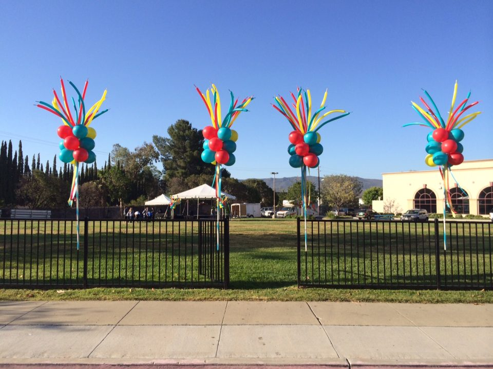 Colorful party poles with wild-look toppers lining a fence at Simi Valley Street Fair